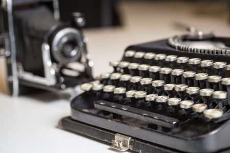 Historical typewriter and camera - artefacts used in the creation of a business history book in the old days and cherished by the team at Canada's leading corporate history agency Historical Branding Solutions Inc.